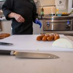 Chef Phillip Dell Cuts Andouille Sausage for Mardi Gras Themed Grilling Class